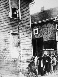 Bystanders attempt to catch moonshine being poured out of a second- story window by federal agents during a raid on an illegal still.