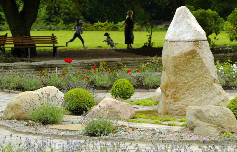 A family plays behind the new Garden of Tranquility in Hyde Park, Greater Manchester, England, which commemorates those who died at the hands of mass murderer Dr. Harold Shipman. PHIL NOBLE/AFP/Getty Images