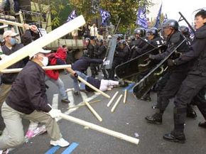 South Korean autoworkers wield clubs against riot police during a 2003 antigovernment rally in downtown Seoul.