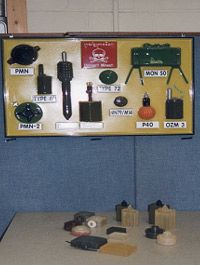 A collection of grenade and landmine replicas designed as training materials.
