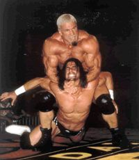 "Scott Steiner puts a victim in his finishing hold, the ""Steiner Recliner"" -- a variation of the camel clutch."