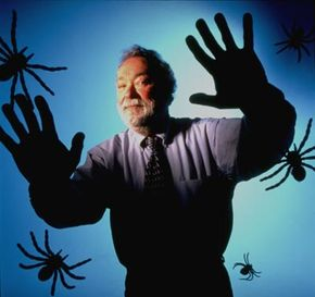 Clinical psychologist Albert Carlin, co-creator of cyber therapy, an approach to treating phobias through virtual reality, posing over a virtual screen peppered with spiders in the University of Washington Human Interface Technology Laboratory.