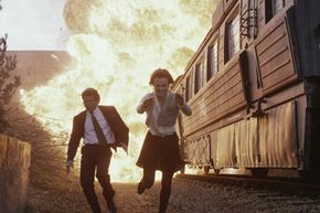 """Pierce Brosnan (as the ever-suave James Bond) and Izabella Scorupco flee from an exploding train in the movie """"Goldeneye."""