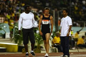 British sprinter Tim Benjamin (center) leaves the track after pulling a hamstring during the men's 400-meters at the 2009 Jamaica International Invitational meet.