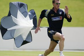 Australian cricketer Brett Lee runs with a parachute, during training at North West Stadium, Potchefstroom, South Africa, on February 3, 2003.