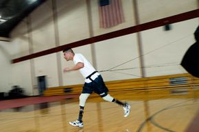 U.S. Marine Sgt. Angel Barcenas, who lost both his legs as a result of and IED blast in Iraq, runs with a parachute during a demonstration at Walter Reed Army Medical Center June 1, 2007 in Washington, DC.