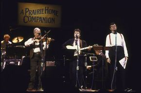 """Garrison Keillor (R), the host of """"A Prairie Home Companion,"""" sings with country fiddler Johnny Gimble and guitarist Peter Ostroushko."""