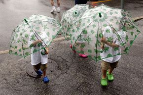 Young triplets with matching frog umbrellas appear ready for any unforeseen weather phenomena.
