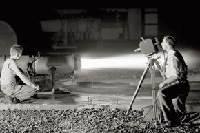 A cameraman with a high-speed camera films the thrust augmentor flame of a ramjet I-40 engine at the Lewis Flight Propulsion Laboratory in Cleveland. (The lab later became known as the John Glenn Research Center.)