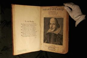 """A Sotheby's employee (very, very carefully) displays a first edition of William Shakespeare's """"First Folio"""" before auction in 2006."""