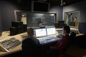 Recording engineers make sure that control panels are running properly before a recording session.