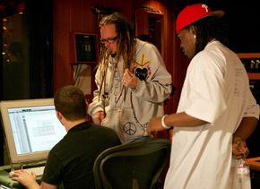 """Recording engineers monitor the control panel during a recording session. Here, Jonathan Davis of Korn, standing left, and Maurice """"Parlae"""" Gleaton of Dem Franchize Boys talk to an engineer. See more recording studio pictures."""