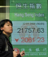 People walk past a stock board displaying the Hang Seng Index in Hong Kong, Jan. 22, 2008.