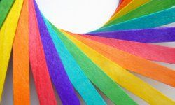 Wooden colored craft sticks, in rainbow colors, arranged in a sweeping spiral pattern.