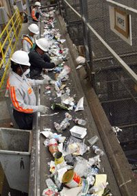 Workers at the Norcal Waste recycling plant sort through materials. The small pieces mixed in will most likely end up as residual.