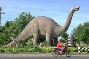 A lone motorist passes by giant dinosaurs erected across the entrance to Thailand's Phu Wiang National Park. See more pictures of dinosaurs.