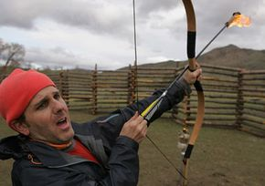 Amazing Race contestant Terry Cosentino shoots a flaming arrow in Mongolia.