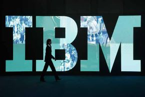 A woman walks past the IBM logo at the 2011 CeBIT technology trade fair in Hanover, Germany. IBM's reinvention is often studied in business schools.