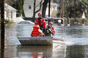 Two women are picked up by the Fairfield firefighter rescue team along the flooded Riveredge Drive in Fairfield, N.J.
