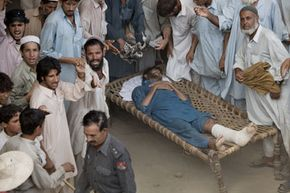 An angry mob gathers around a man beaten by Pakistani police. The man had asked for food rations in the midst of a food shortage.