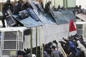 An angry mob confronts riot police in South Korea.
