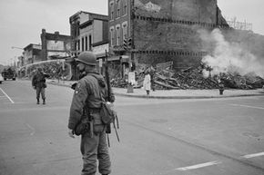 A soldier surveys the aftermath of rioting following the death of Martin Luther King Jr.