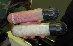 These shells are loaded into the pepperball gun. The top shell contains pellets loaded with pepper spray, while the bottom shell contains water pellets.
