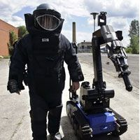 A police bomb disposal expert walks with a remote controlled police robot.