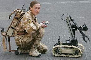 """Captain Judith Gallagher displays an anti-IED robot known as the """"Dragon Runner"""" in London. The robot fits in a backpack and has a camera to look under and around vehicles and other obstacles. The images are sent to a control center in real time. See more robot pictures."""