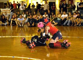 Opposing jammers come to blows during a bout. This major penalty led to time in the penalty box and a backwards-skating race.