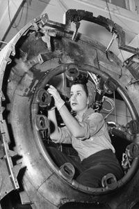 A woman works inside a cylinder at an arms manufacturing plant.