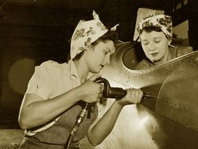 Like Rosie, this woman is a true riveter. She drivesrivets into an aircraft while her co-worker sits in the cockpit.