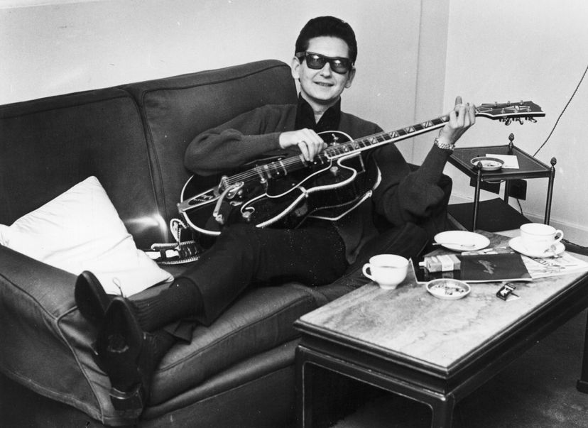 singer roy orbison reclines on a couch holding a guitar