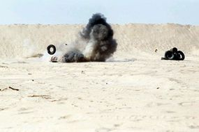 A round from an M-72 light anti-tank weapon (LAW) destroys a target at Abu Hydra Range as Marines from 7th Platoon, 1st Force Reconnaissance Company, and British soldiers from the Queen's Dragoon Guards conduct weapons training during Operation Desert Shield.