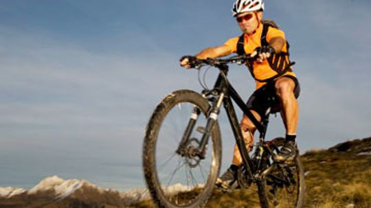 Should I stand or sit when riding uphill?