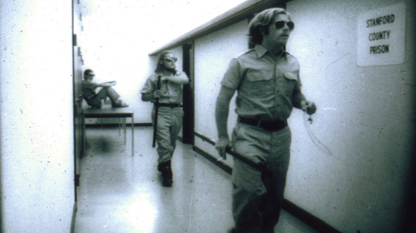 """Guards walk through the prison """"yard,"""" the school hallway. It didn't take long for the experiment to spiral out of control. PrisonExp.org"""