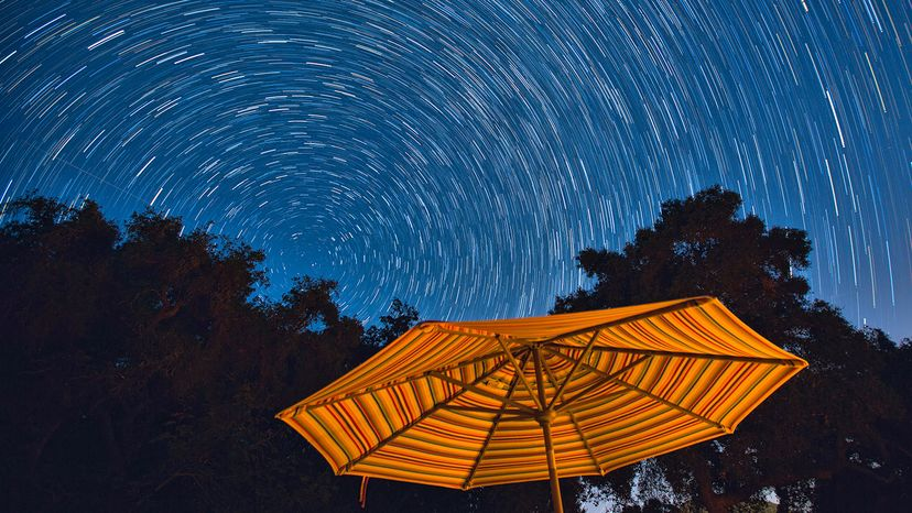 Star trails at night with orange umbrella in foreground