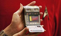 """A Christies New York employee holds a replica of a newer-model tricorder in London on Aug. 2, 2006, as part of a """"Star Trek"""" 40th anniversary celebration."""
