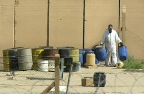 A UN International Atomic Energy Agency (IAEA) scientist carries barrels at the Tuwaitha nuclear plant, near Baghdad, where a team of seven is making an inventory of the nuclear material which was under its safeguard at the site before the war.