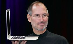 Apple CEO and co-founder Steve Jobs holds up a Mac Book Air.