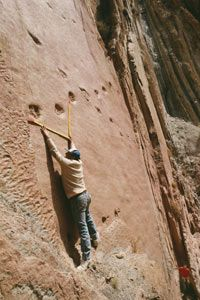 Anthropologist Ricardo Alonso precariously measures dinosaur tracks in Argentina. See more dinosaur pictures.