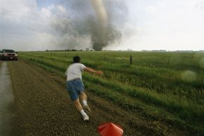 Near Woonsocket, S.D., a storm chaser plants a weather probe in the path of a tornado.