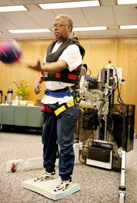 A stroke victim works with a robotics device that assists with balance during physical therapy.