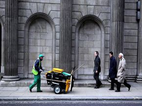 An old-school street-sweeper at work in front of London's Bank of England.