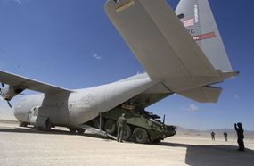 A Stryker Mortar Carrier exits the tail of an Air Force C-130 Hercules aircraft after landing at Bicycle Lake Army Airfield at the National Training Center, Fort Irwin, CA.