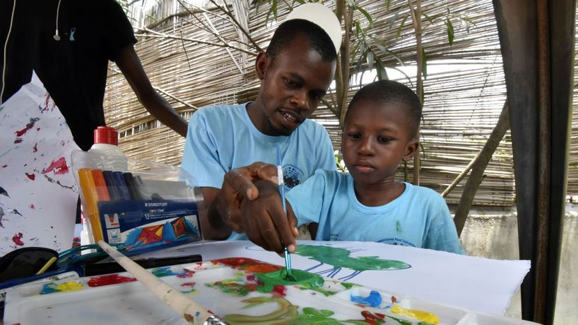 A man helps a child with autism to paint in Abidjan, Ivory Coast. Parents of children with autism are likelier to recall their child was immunized prior to showing signs of autism and draw a connection, even if incorrect -- an example of recall bias SIA KAMBOU/AFP/Getty Images