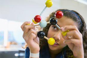 An elementary student examines a molecular model.