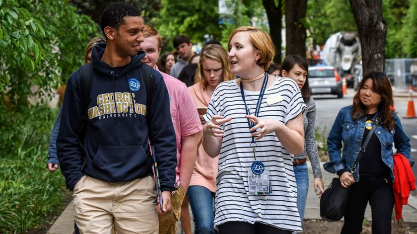 Sophomore Paige James, center right, talks with Max Stanley, left, of Glasgow, New Jersey, as she leads admitted George Washington University students and their parents on a tour of the campus. GW is a private university. Bill O'Leary/The Washington Post via Getty Images