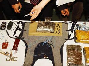 Uzbek officials display confiscated homemade bombs, guns and suicide vest