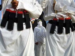 Masked Islamic militants wear fake explosive belts during a 2002 rally in Gaza City.
